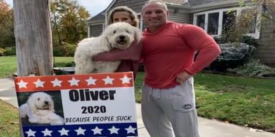 due-persone-con-in-braccio-un-cane-e-cartello