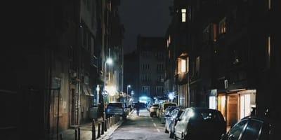 hombre camina por una calle oscura con coches aparcados