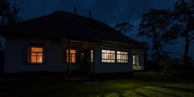 Dom w nocy z oświetlonymi oknami