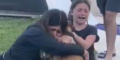 Girls hugging dog