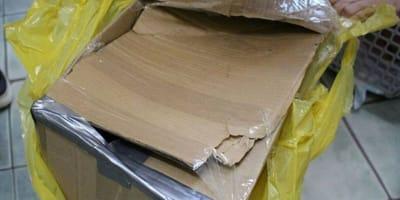 scatola di cartone danneggiata all'interno di un sacchetto di plastica