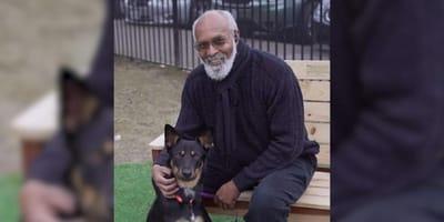 un perro sentado junto a su dueno en un banco