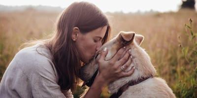 mujer besa a un perro en la cabeza
