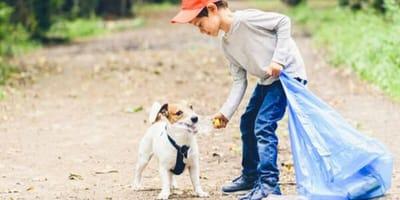 niño junto a perro comiendo bolsa plastico
