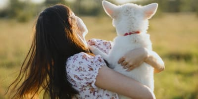 woman holding white dog in her arms