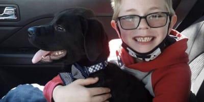 niño abrazando a su perro negro